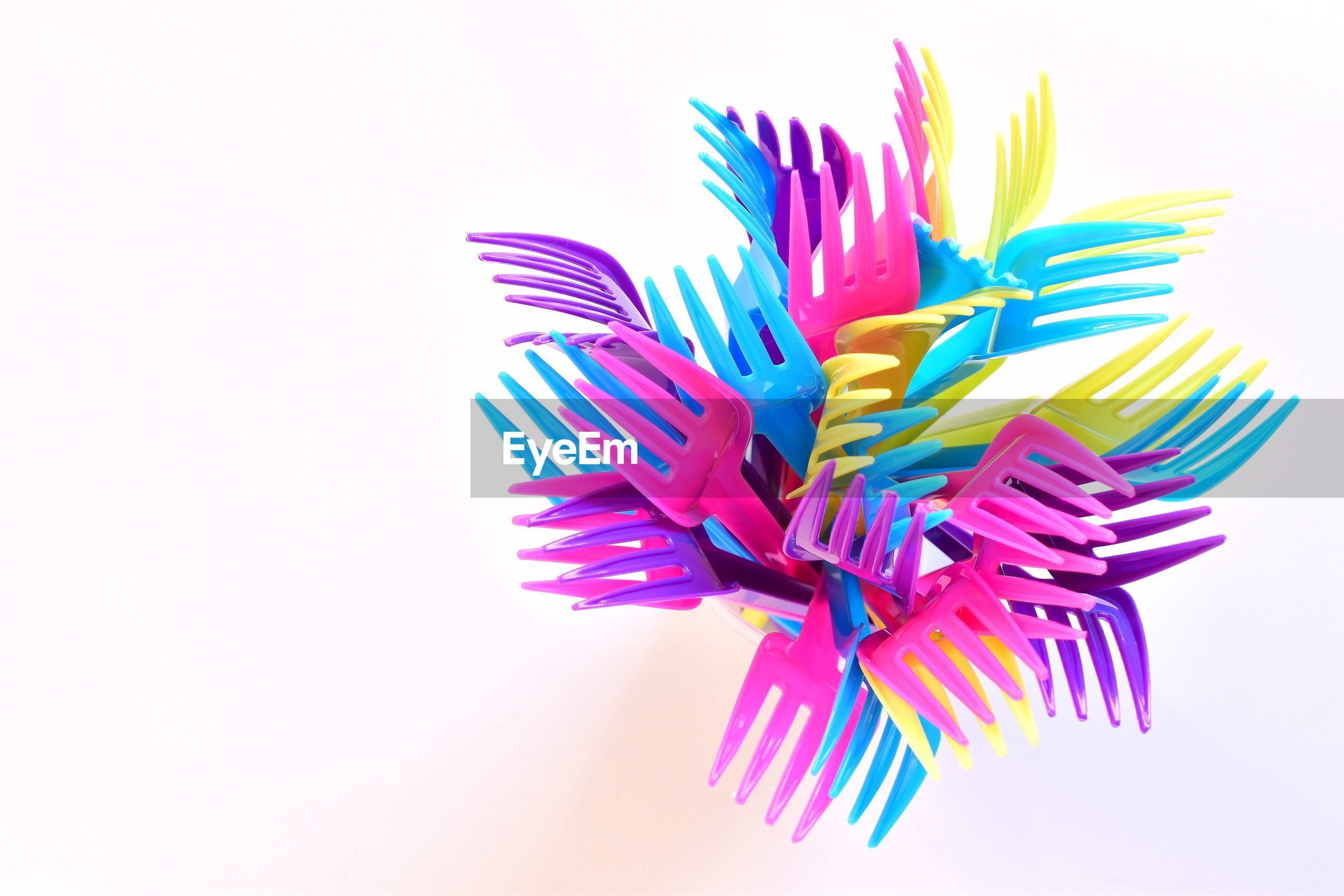 Directly above shot of colorful forks on white background