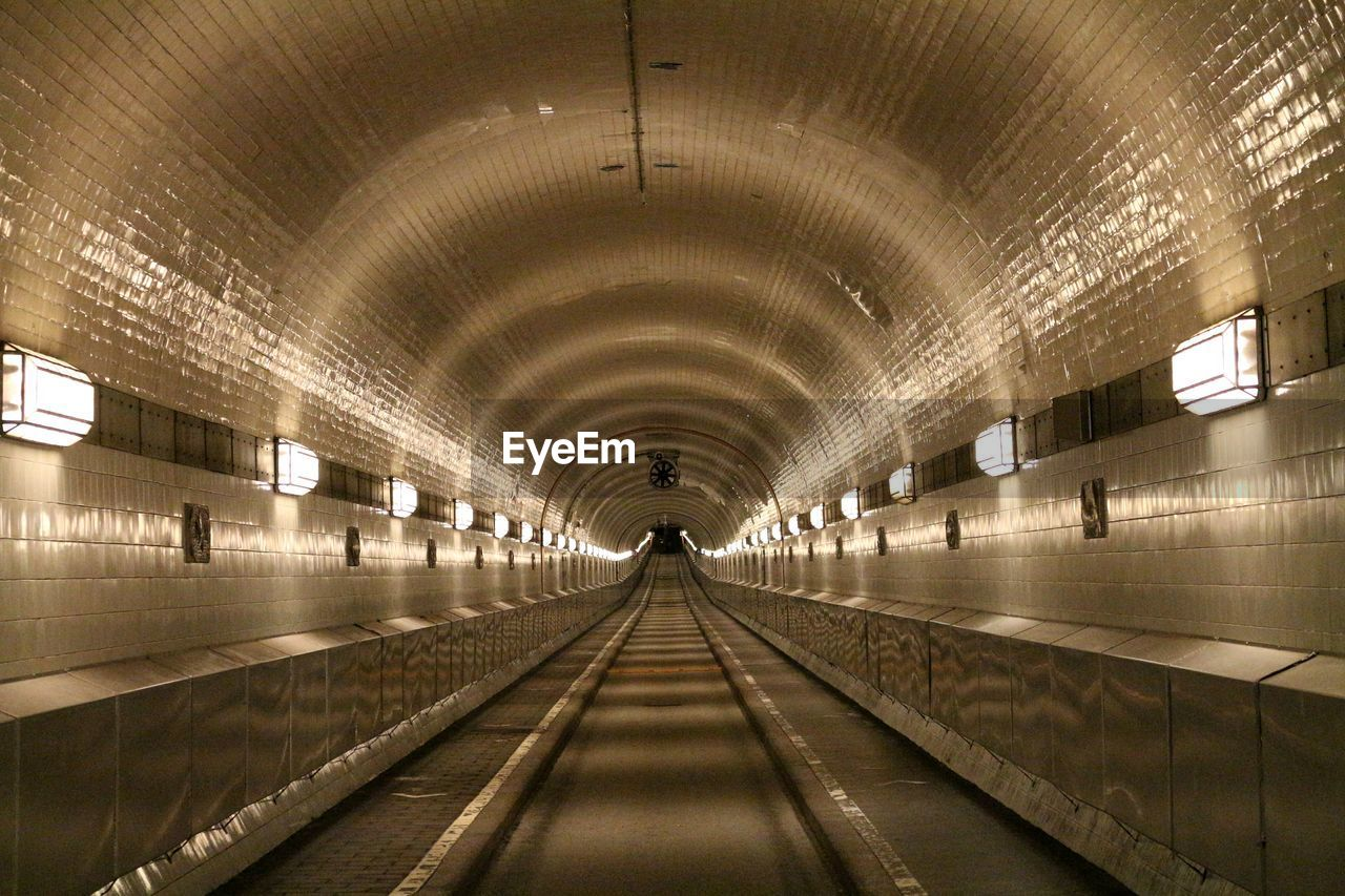 illuminated, direction, the way forward, lighting equipment, transportation, architecture, indoors, ceiling, diminishing perspective, public transportation, subway, tunnel, built structure, arch, flooring, no people, empty, subway station, light, rail transportation, light fixture, underpass, long, underground walkway, arched