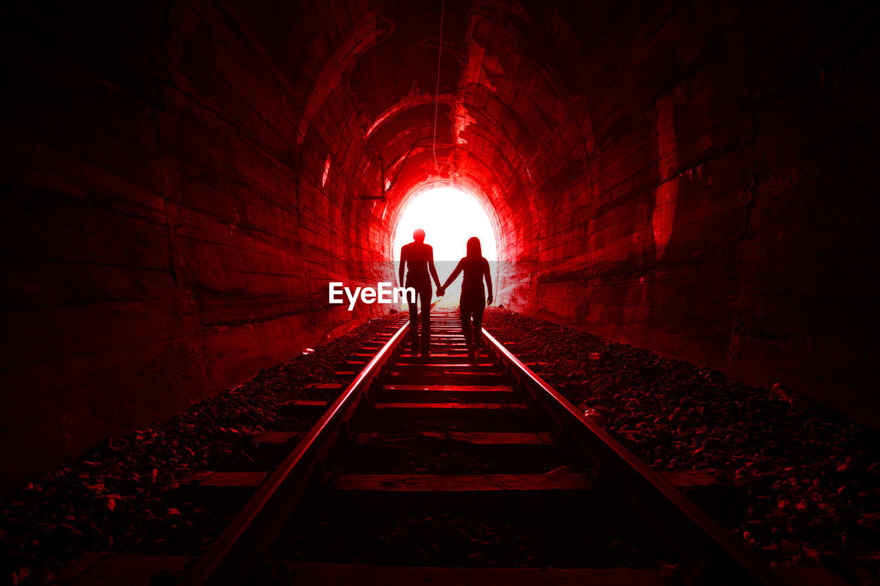 Silhouette Man And Woman Standing On Railroad Track In Tunnel