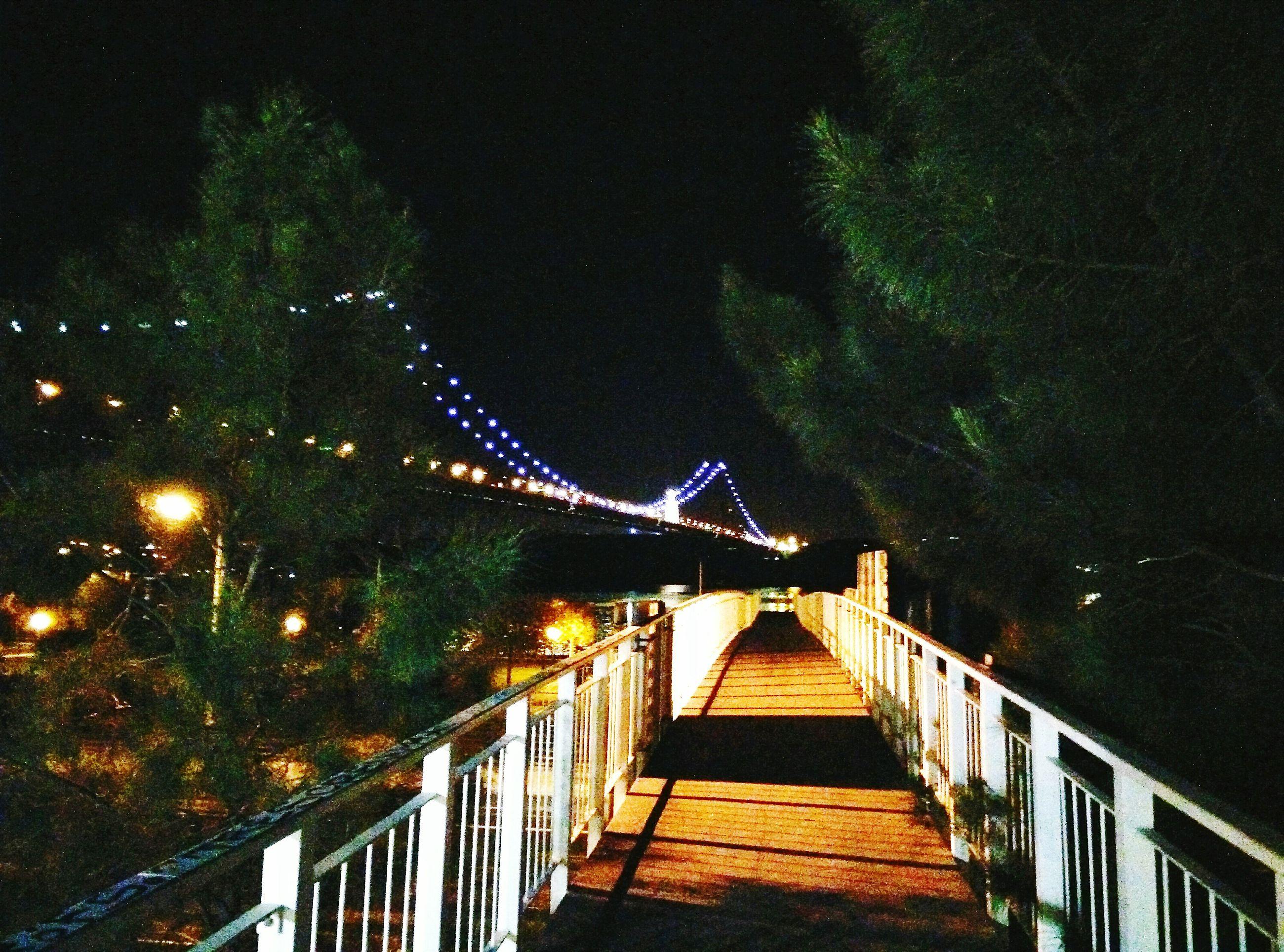 Footbridge leading towards illuminated bridge