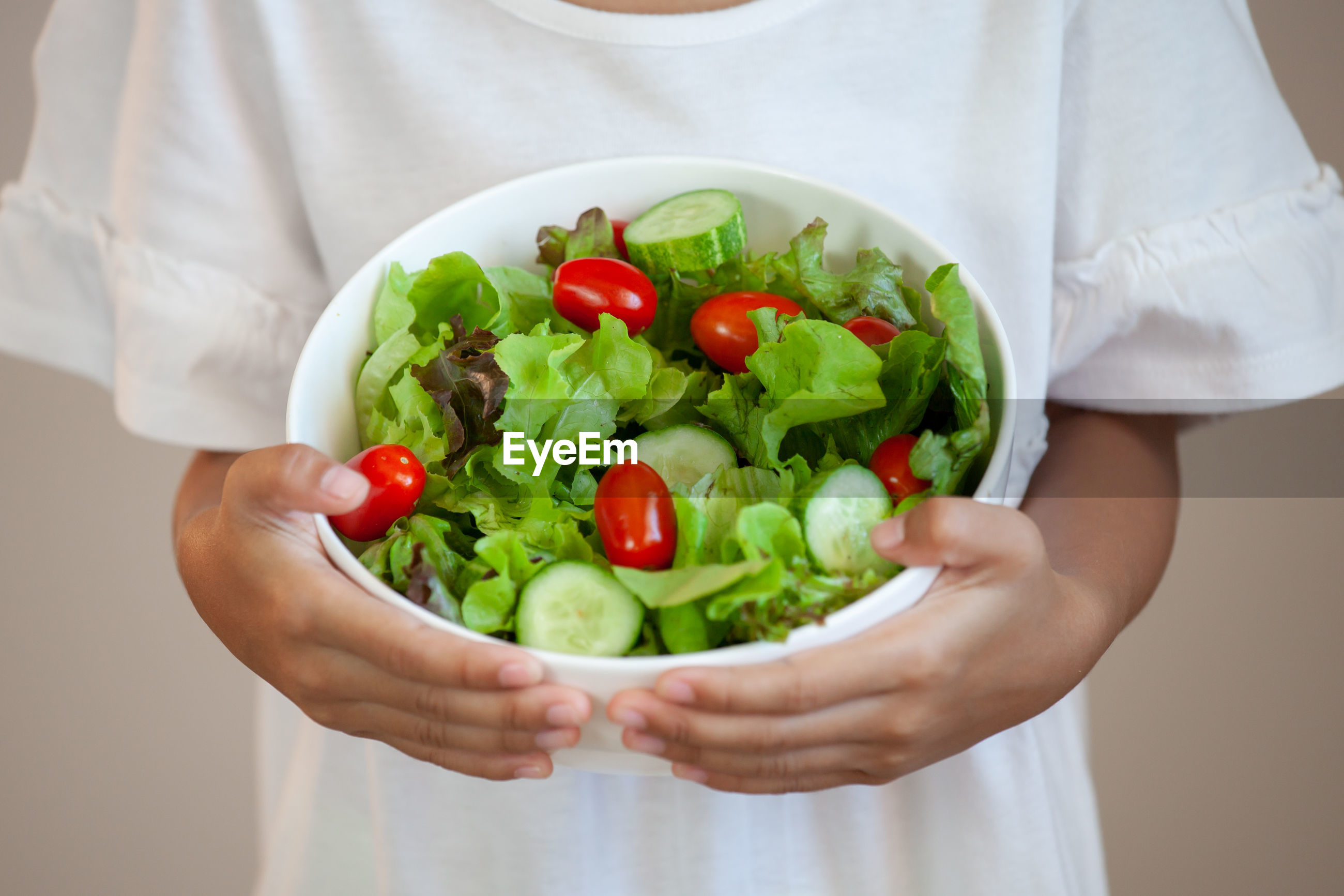 Midsection of girl holding salad in bowl
