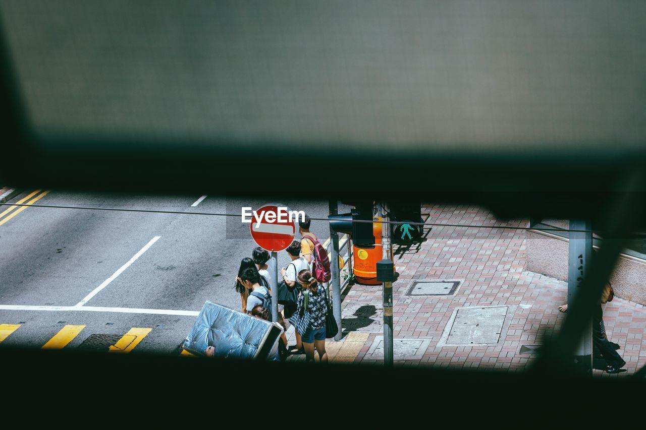People Standing On Sidewalk Seen Through Railing