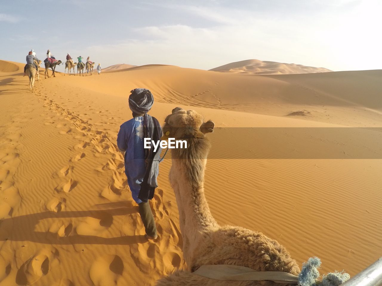 People Riding Camels In Desert Against Sky