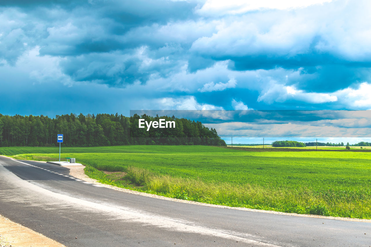 road, cloud - sky, sky, green color, scenics, tranquility, the way forward, day, nature, grass, transportation, beauty in nature, tranquil scene, outdoors, tree, no people, landscape, field, growth, rural scene