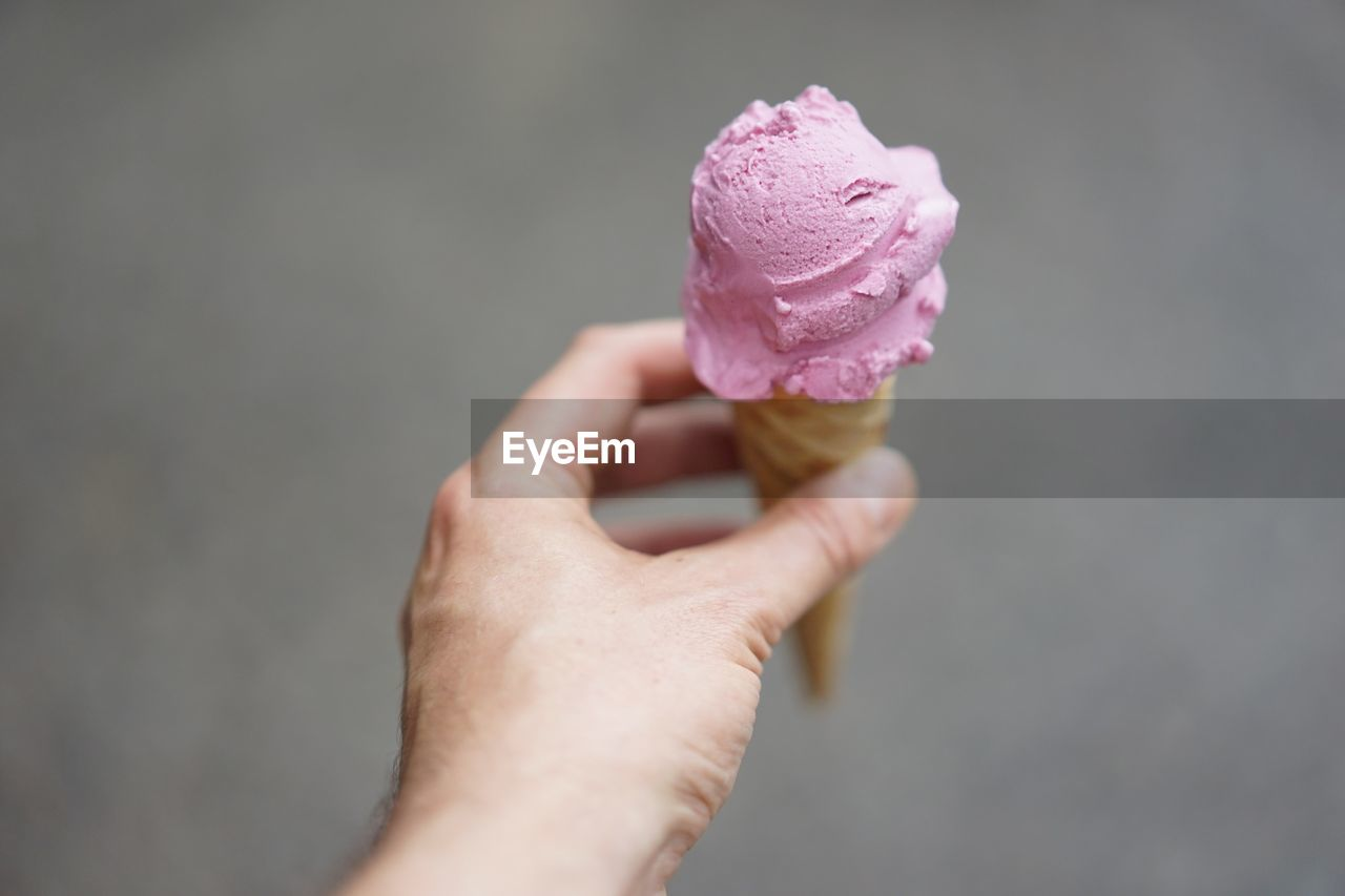 Male hand holding ice cream cone against gray background