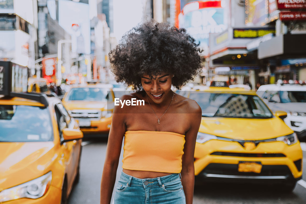 Young Woman With Afro Hairstyle Standing On City Street