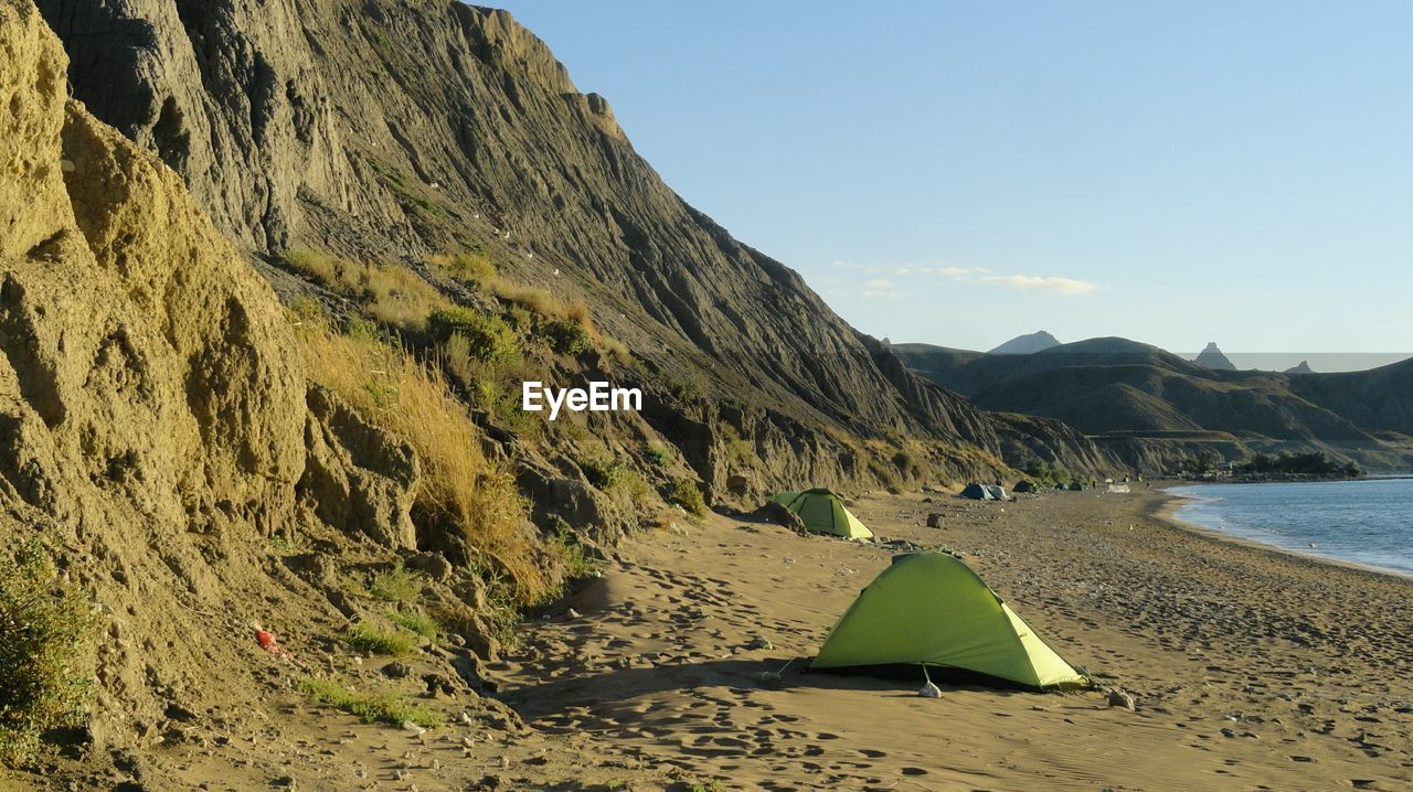 mountain, water, sky, land, beach, beauty in nature, scenics - nature, nature, tranquility, sand, sea, day, tranquil scene, no people, mountain range, non-urban scene, sunlight, outdoors, idyllic