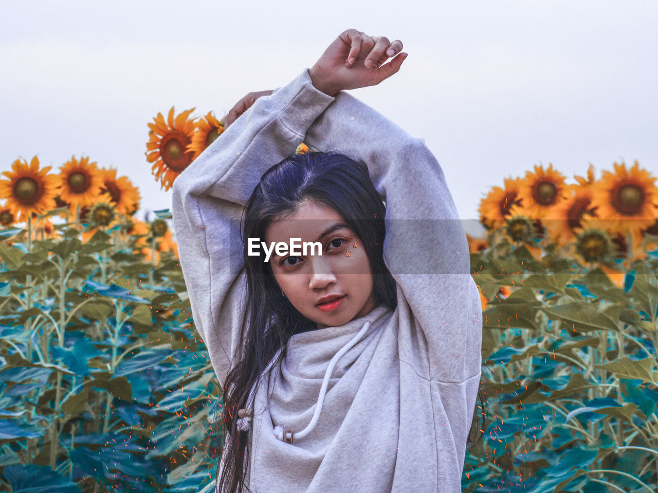 one person, real people, portrait, looking at camera, front view, child, waist up, lifestyles, plant, leisure activity, girls, childhood, standing, casual clothing, flowering plant, flower, nature, day, outdoors, human arm, teenager, hood - clothing