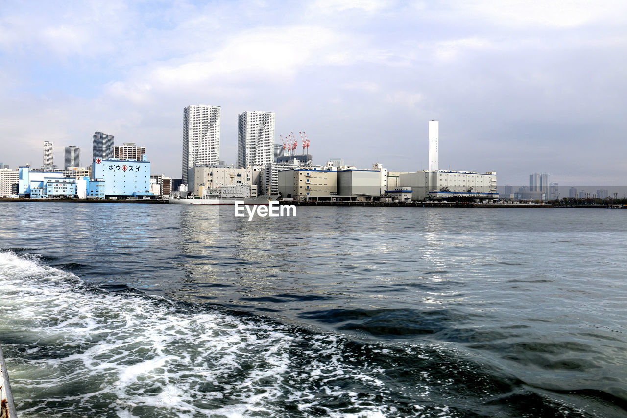 skyscraper, sea, architecture, sky, built structure, building exterior, water, cloud - sky, city, waterfront, modern, day, urban skyline, no people, cityscape, downtown district, outdoors, nature, commercial dock