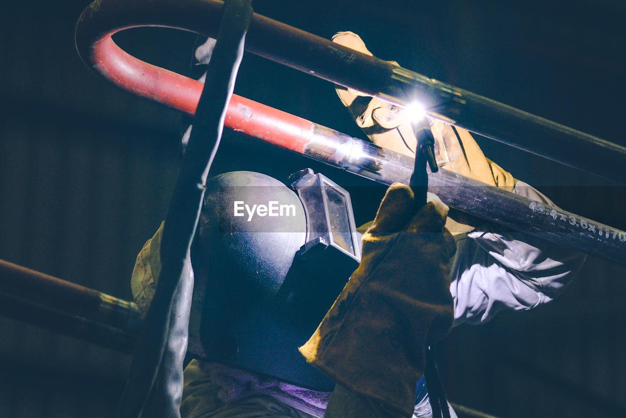 Close-up of welder welding in factory