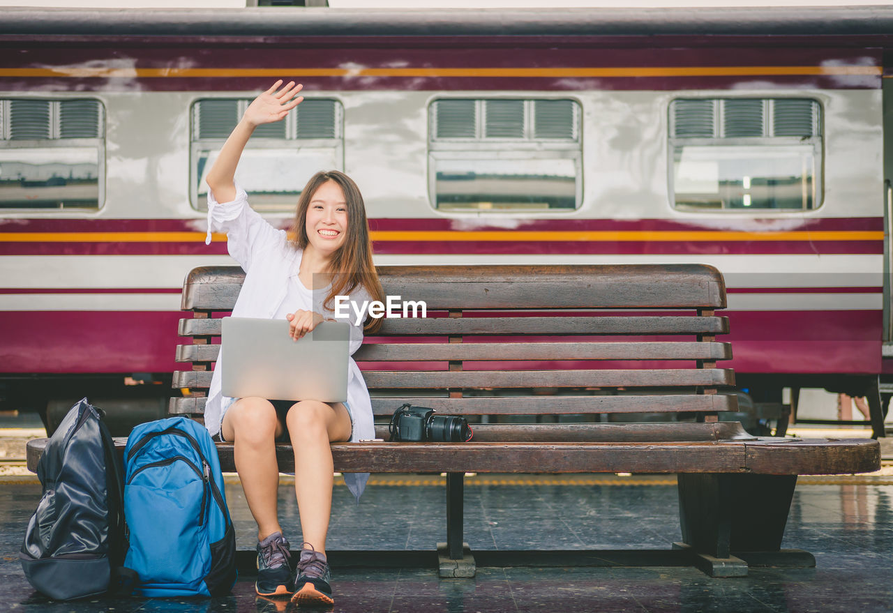 Portrait of smiling woman with laptop sitting on bench at railroad station platform