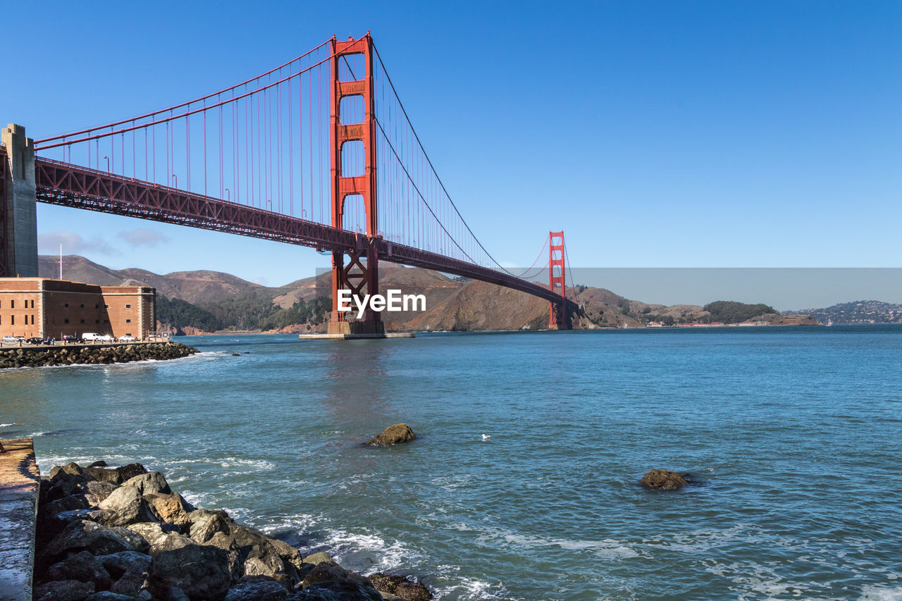 Low Angle View Of Golden Gate Bridge Over Sea Against Clear Blue Sky