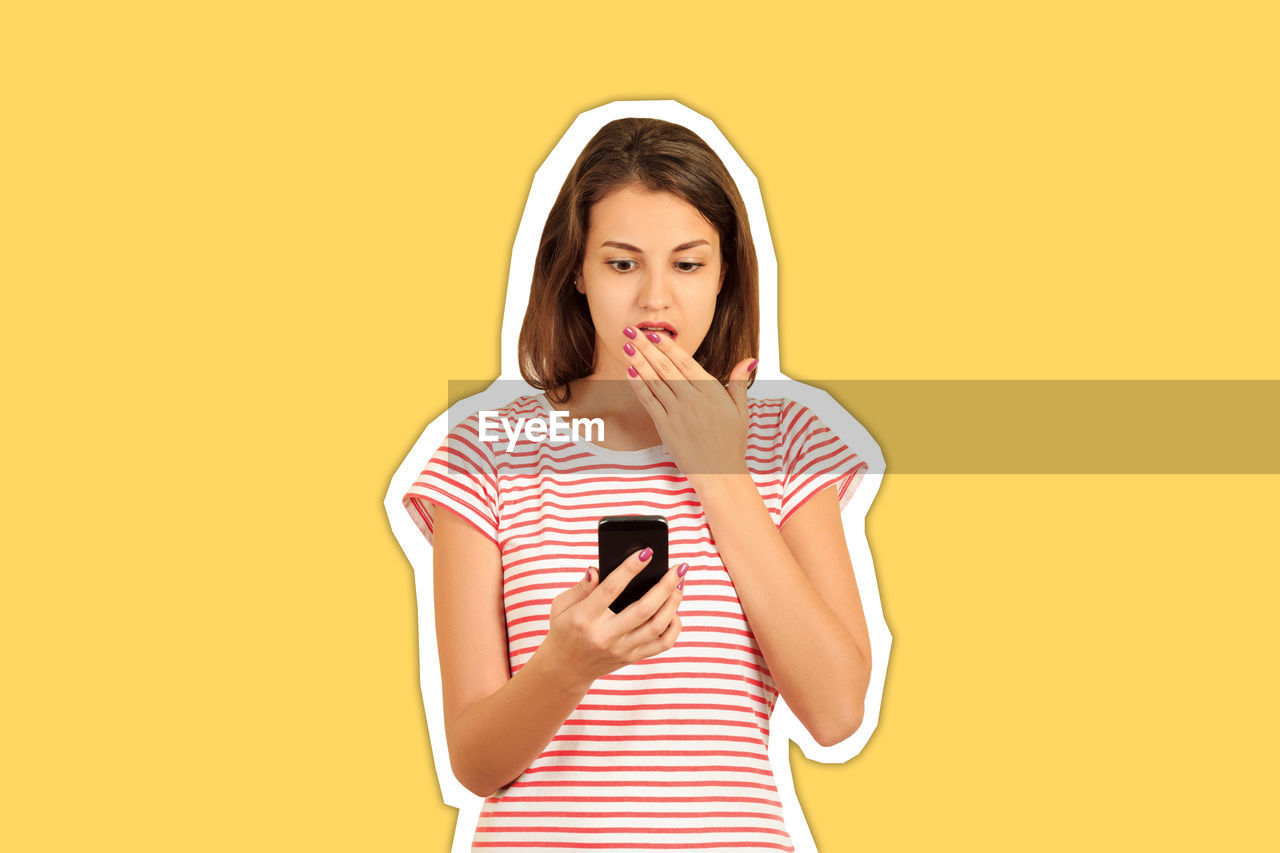 Shocked young woman holding mobile phone cut out against yellow background