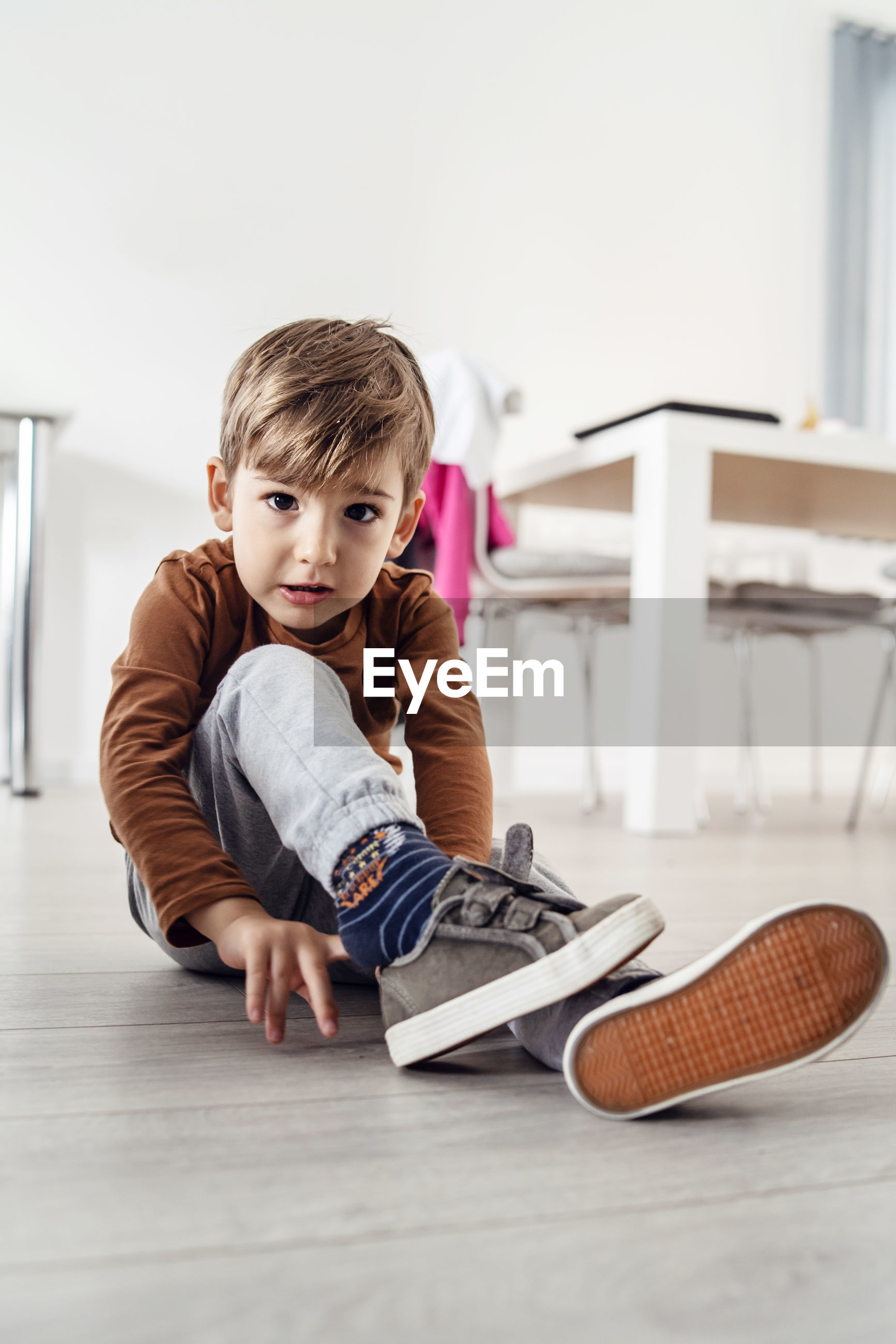 Portrait of cute boy wearing shoes while sitting on floor at home