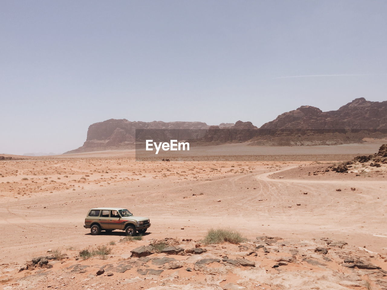 Off-Road Vehicle On Desert Against Clear Sky