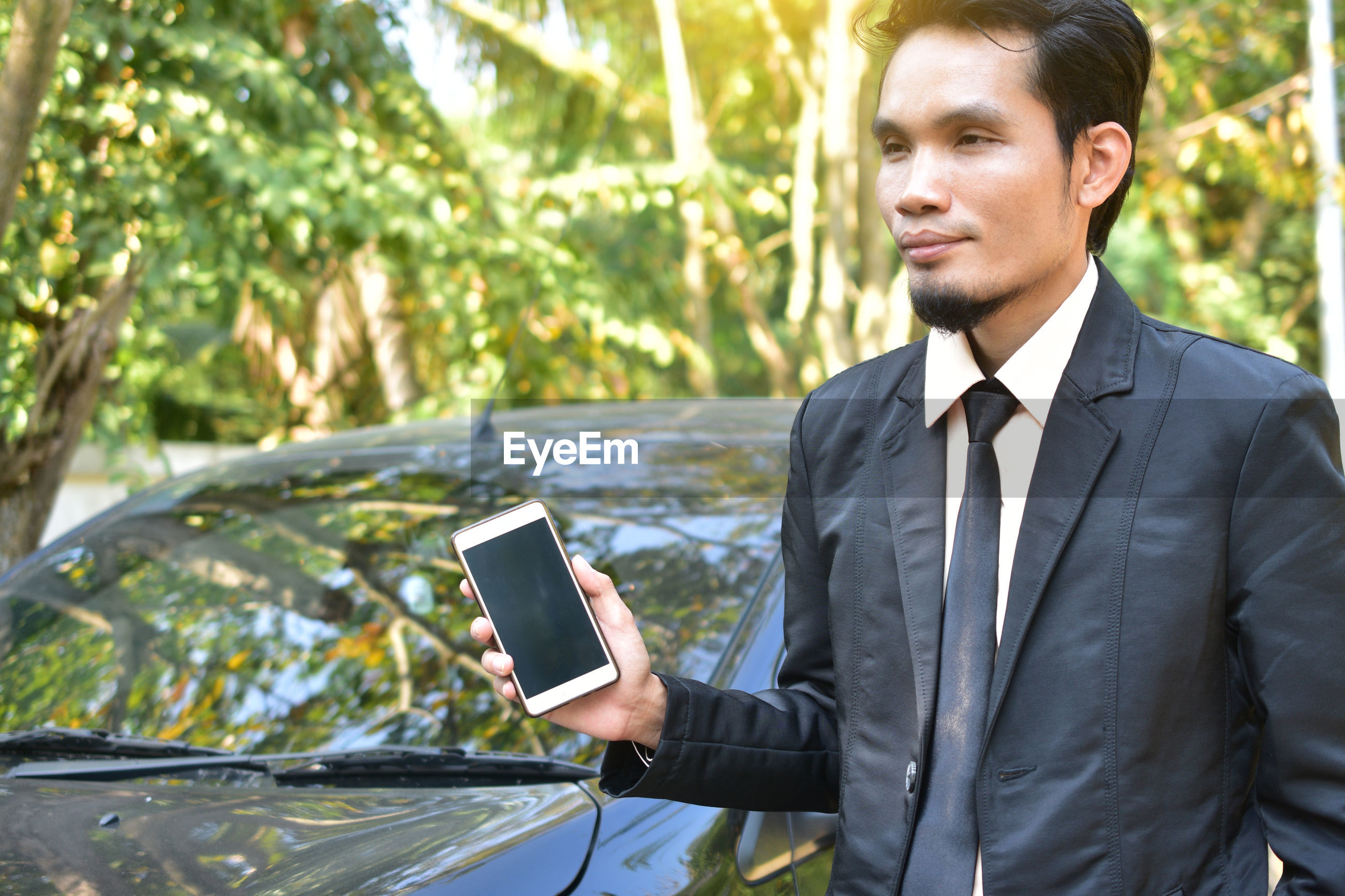 Businessman holding mobile phone while standing by car