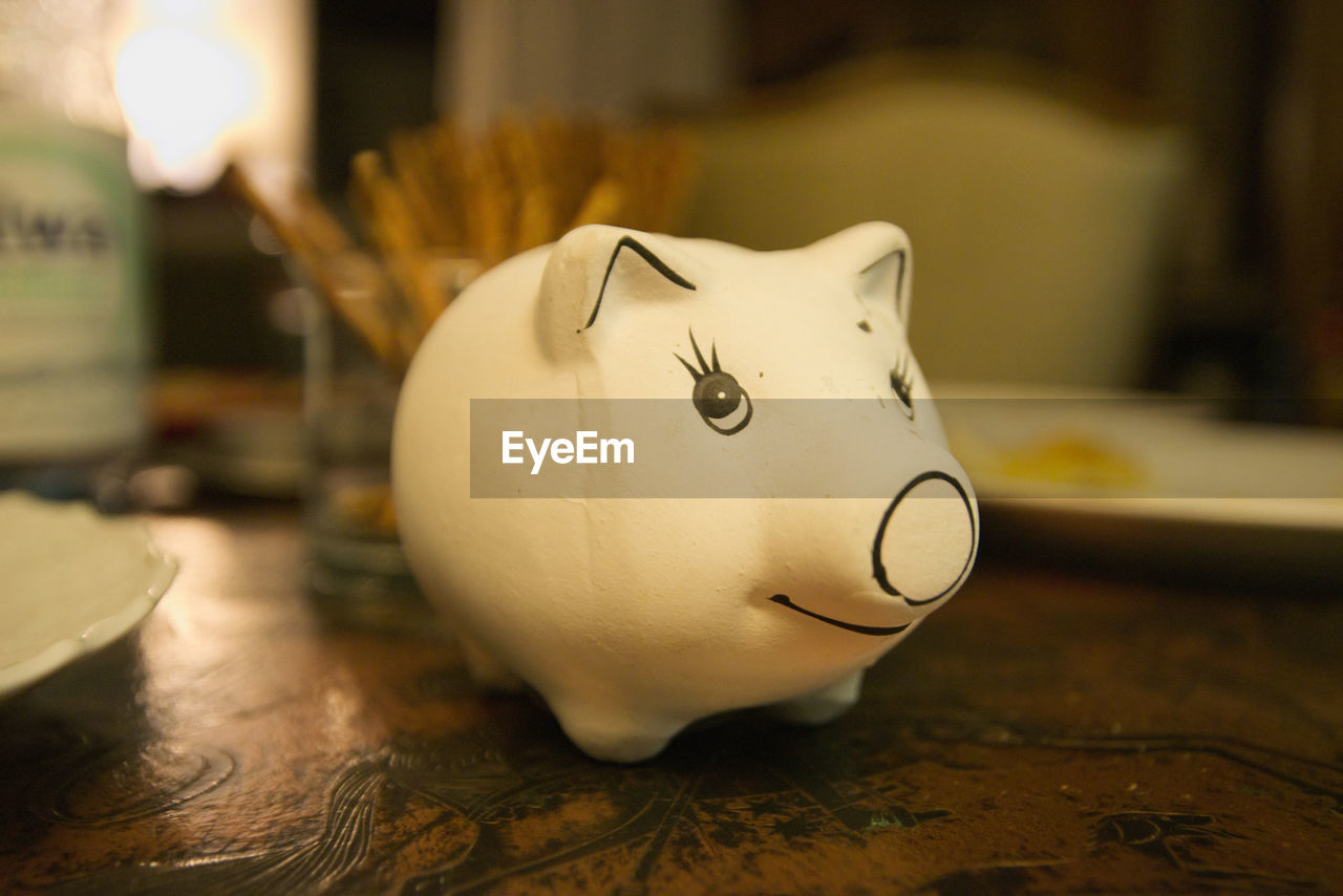 Close-Up Of White Piggy Bank On Table