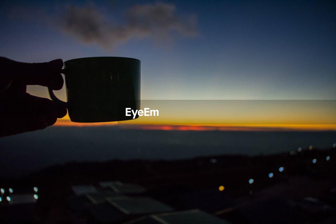 CLOSE-UP OF HAND HOLDING CAMERA AGAINST SUNSET SKY