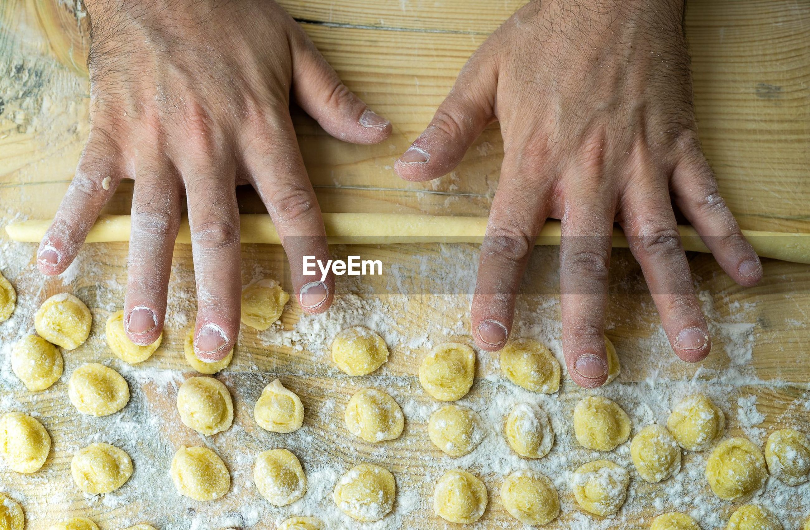Cropped hands of man rolling dough on wooden table