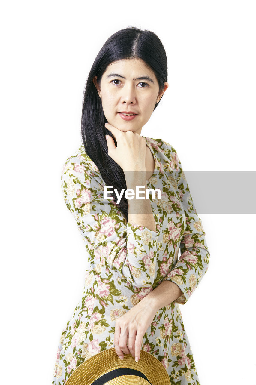white background, portrait, looking at camera, studio shot, one person, indoors, young adult, cut out, three quarter length, young women, women, adult, beautiful woman, black hair, front view, hair, hairstyle, beauty, sitting, fashion, floral pattern