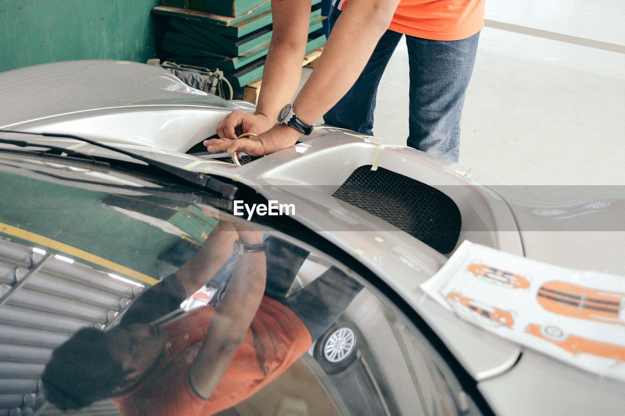 Midsection Of Man Repairing Car