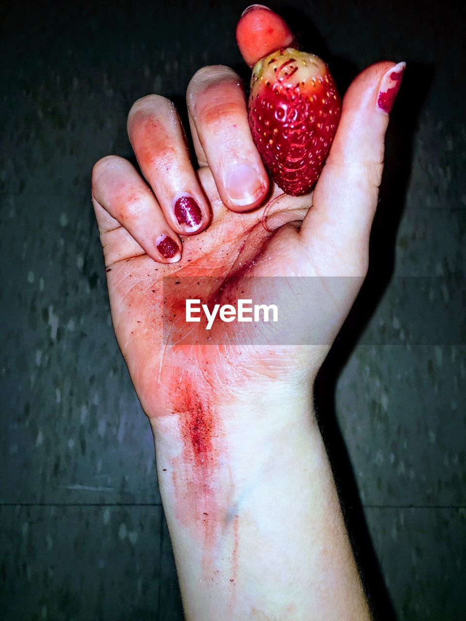 Close-Up Of Bloody Hand Holding Strawberry Against Wall