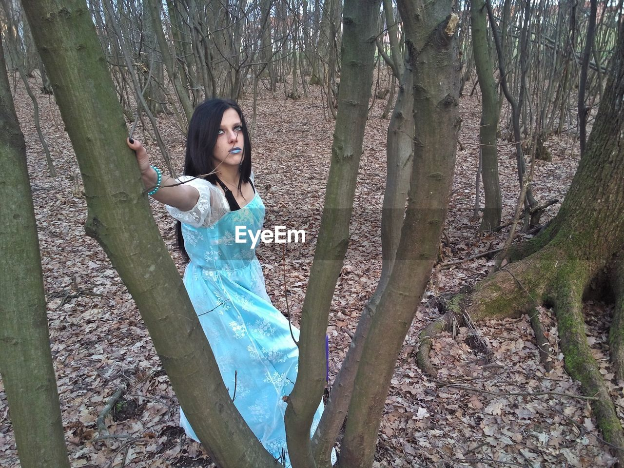 Woman standing amidst trees at forest