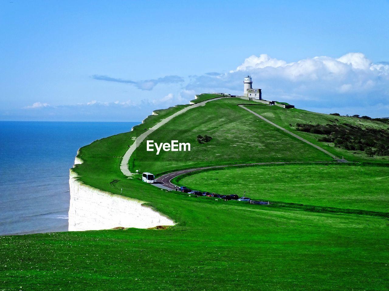 Distance shot of lighthouse against calm blue sea