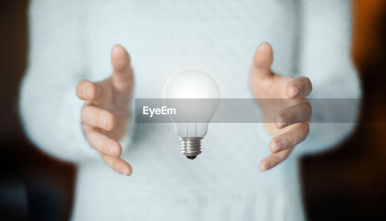 light bulb, one person, hand, human hand, human body part, lighting equipment, indoors, focus on foreground, holding, close-up, real people, body part, front view, electricity, glass - material, midsection, showing, unrecognizable person, finger
