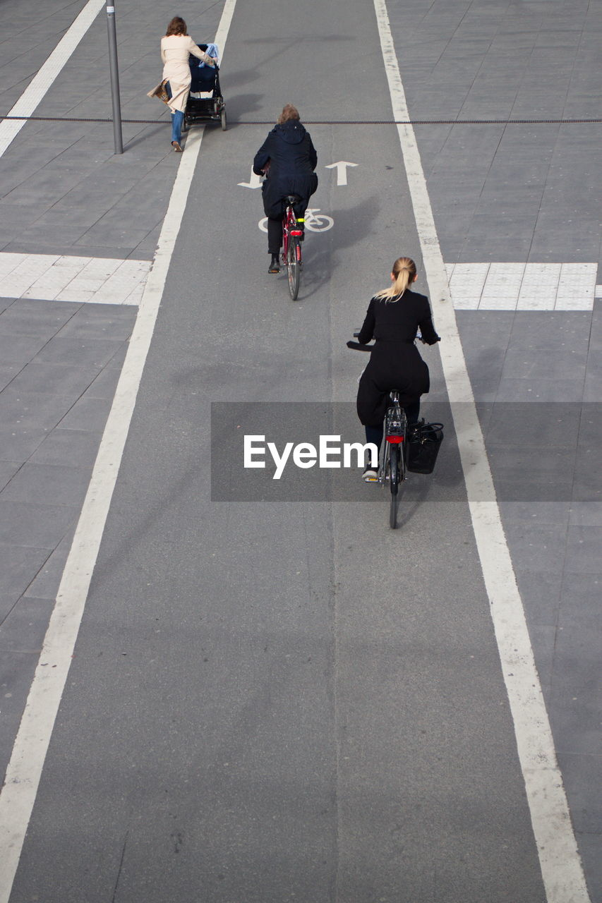 Two Women Riding Bicycles On Street
