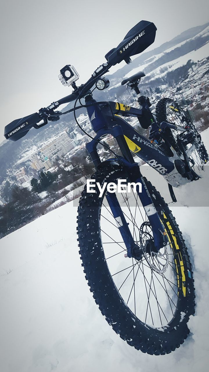 transportation, snow, mode of transportation, bicycle, land vehicle, winter, cold temperature, nature, mountain, sky, day, sport, travel, no people, outdoors, stationary, adventure, low angle view, beauty in nature, wheel, snowcapped mountain