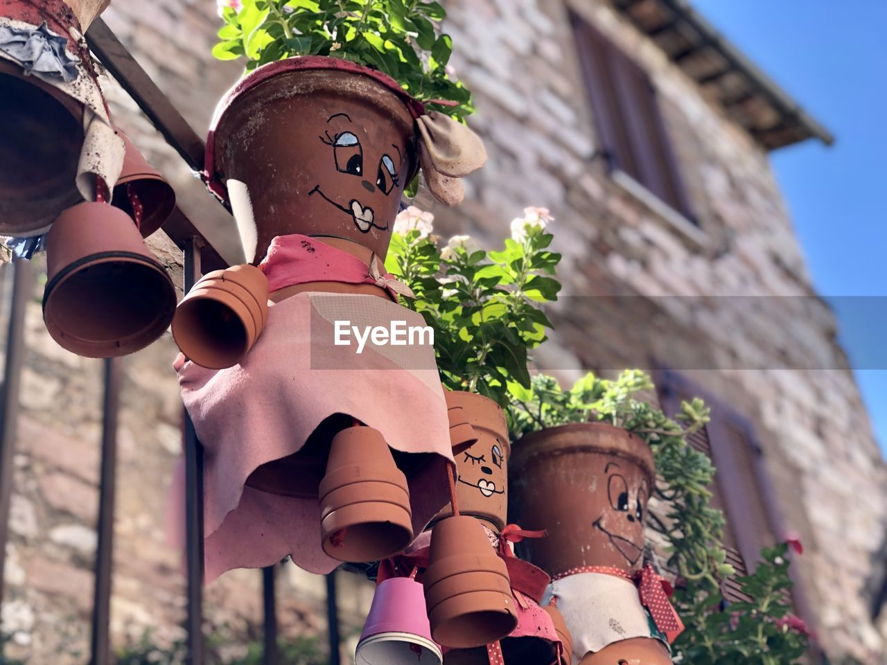 architecture, built structure, building exterior, low angle view, day, nature, human representation, building, representation, plant, focus on foreground, art and craft, creativity, real people, outdoors, childhood, child, male likeness, lifestyles, men