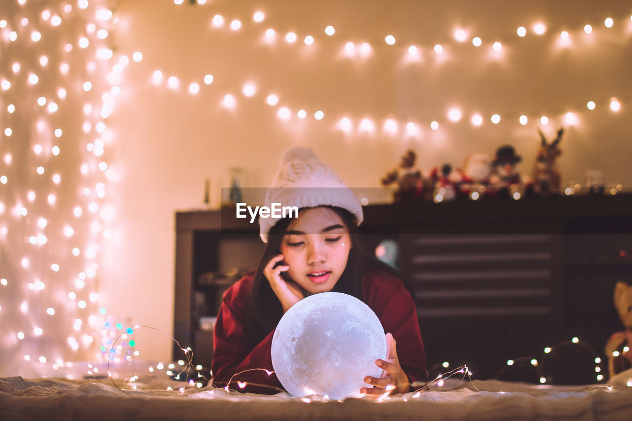 Smiling Woman With Crystal Ball At Illuminated Home During Christmas