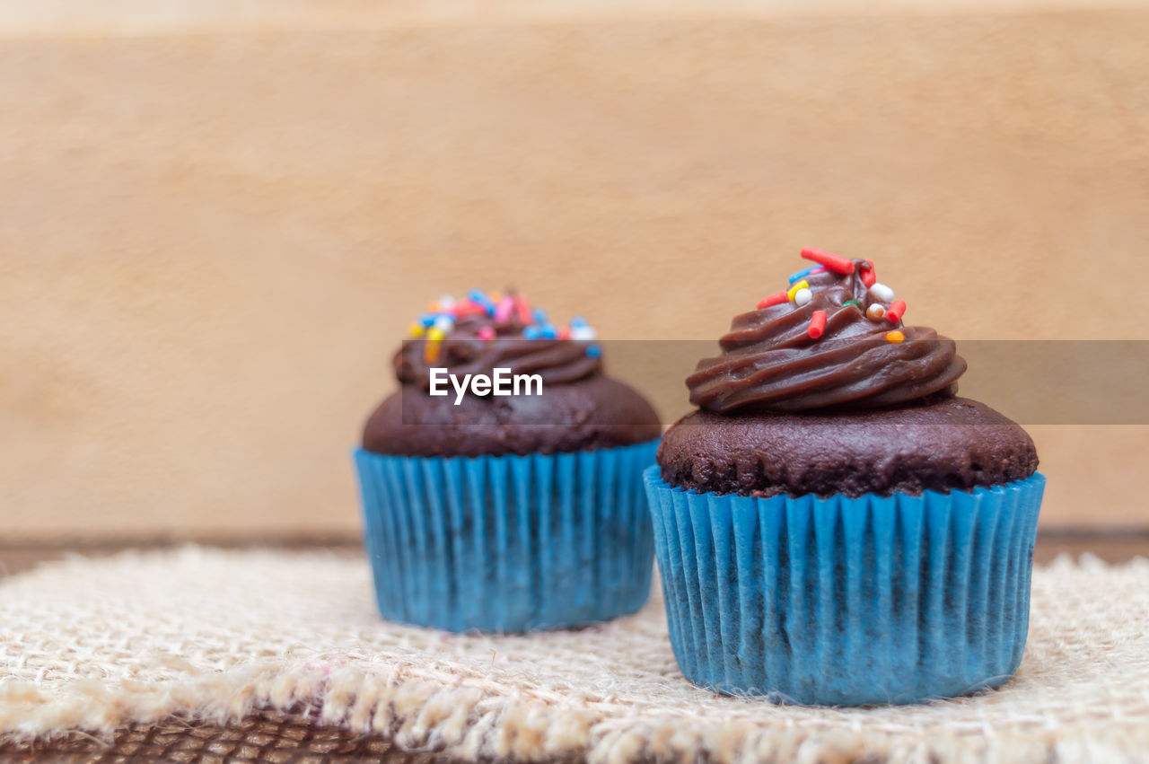 sweet food, indulgence, cake, food and drink, cupcake, food, temptation, dessert, sweet, ready-to-eat, baked, freshness, close-up, indoors, table, focus on foreground, still life, no people, unhealthy eating, sprinkles, icing, cupcake holder, muffin