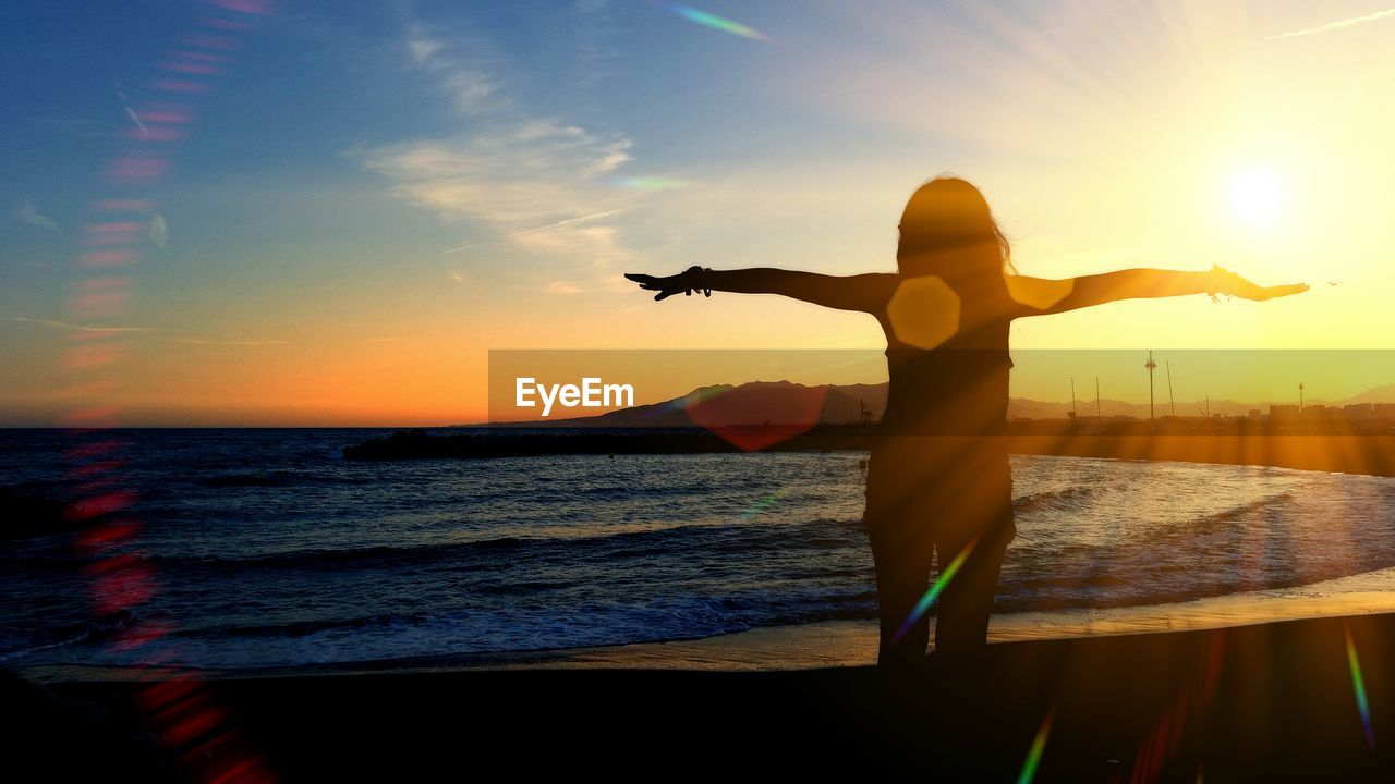 Rear view of woman with arms outstretched while standing on beach during sunset