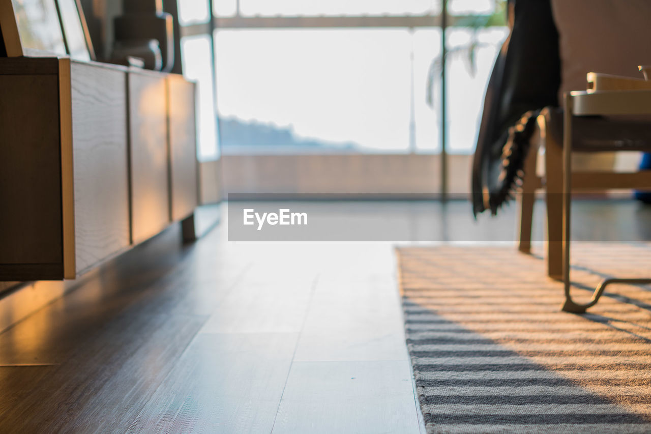 day, indoors, flooring, sunlight, absence, seat, no people, chair, entrance, business, door, table, focus on foreground, nature, empty, window, architecture, tiled floor, furniture