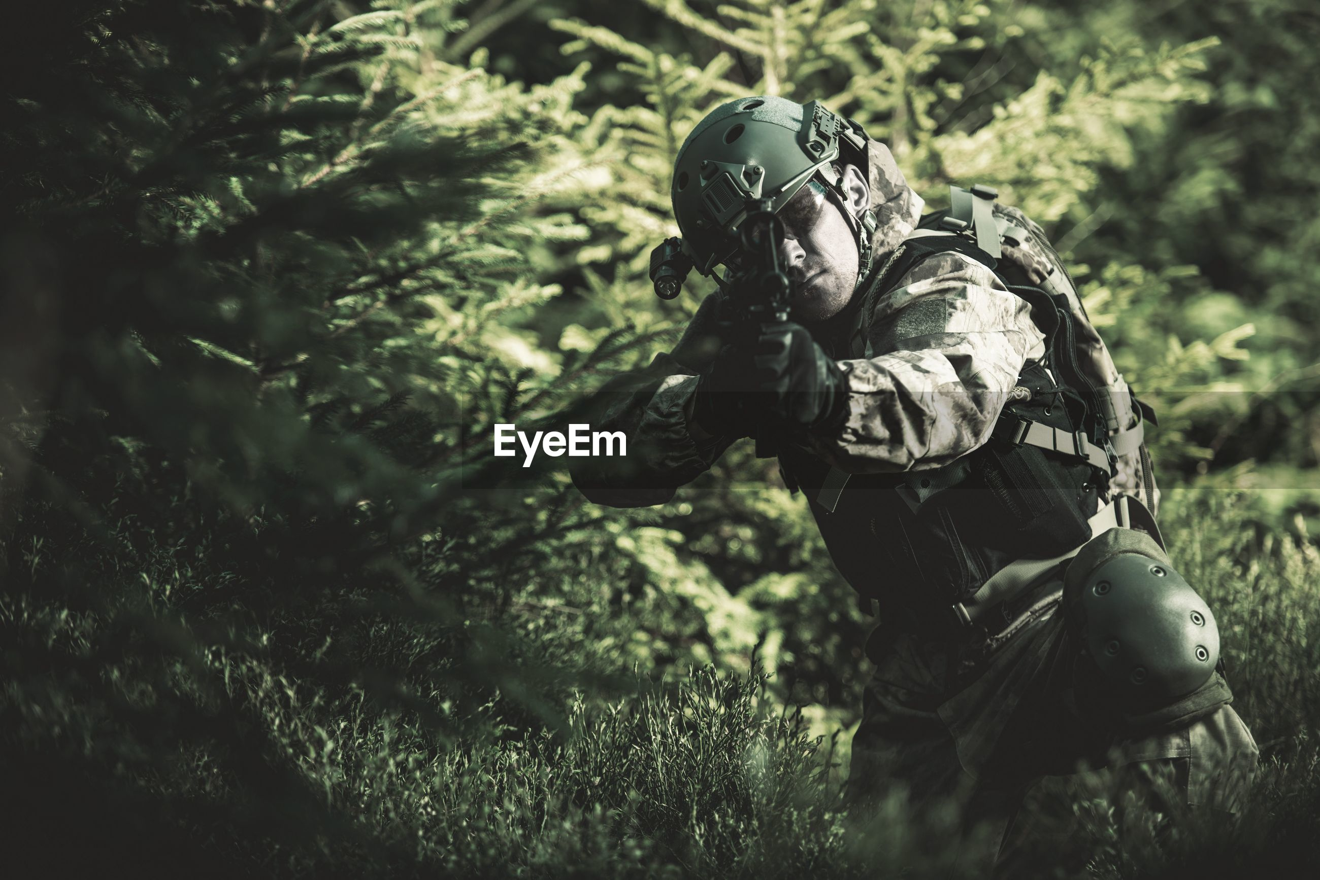 Soldier aiming gun while standing in forest
