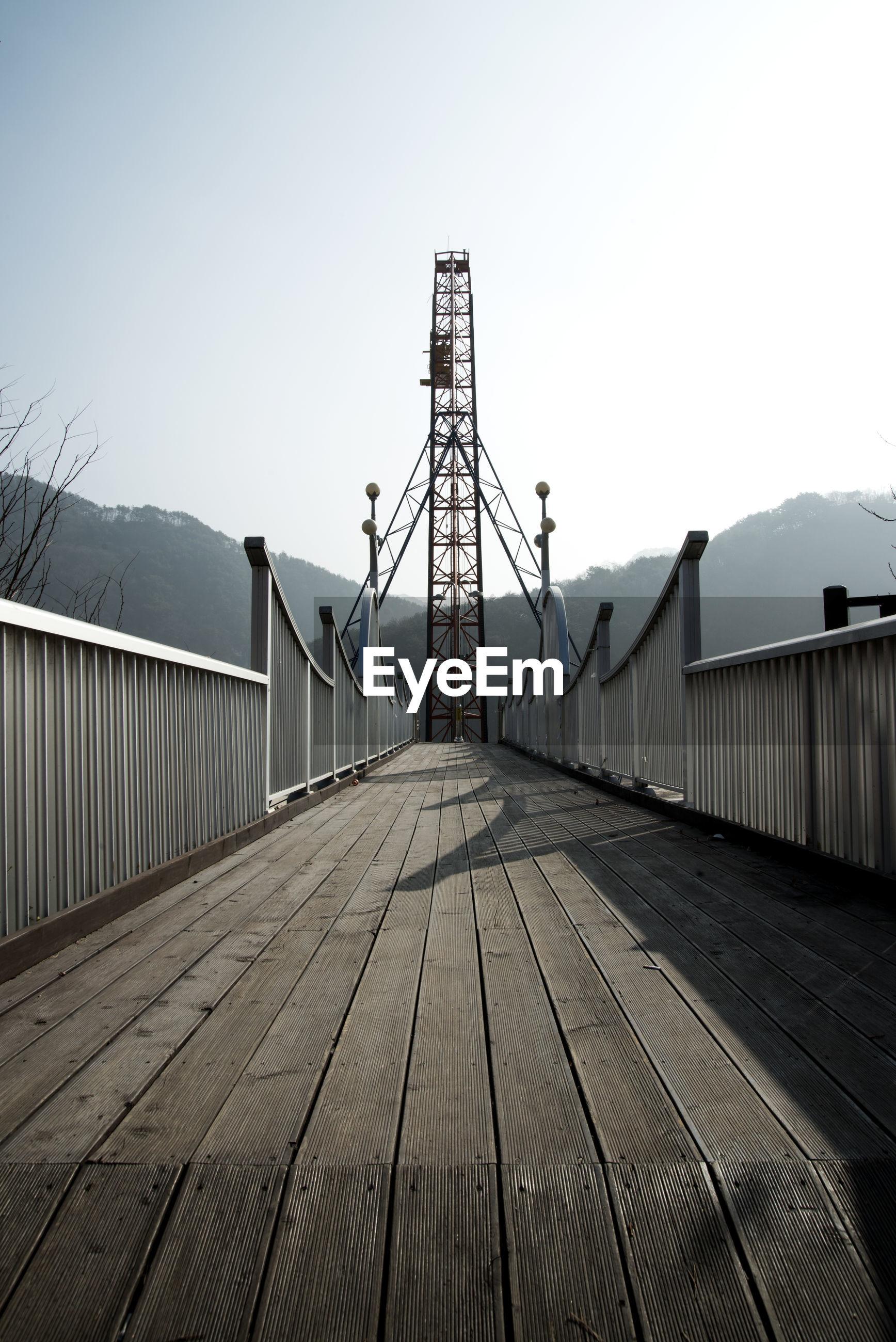 Footbridge leading to metallic tower against sky