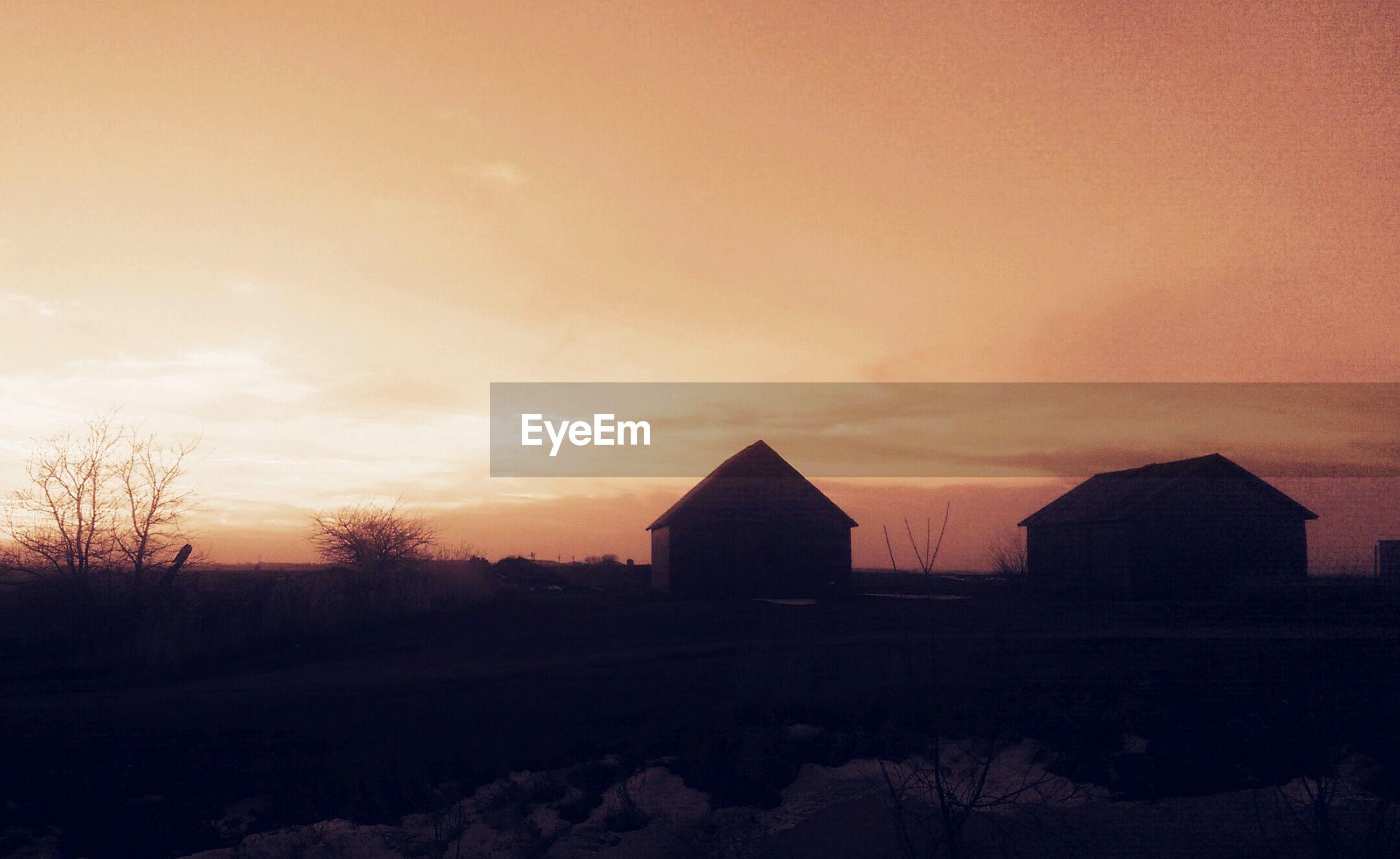 Silhouette houses on landscape at dusk
