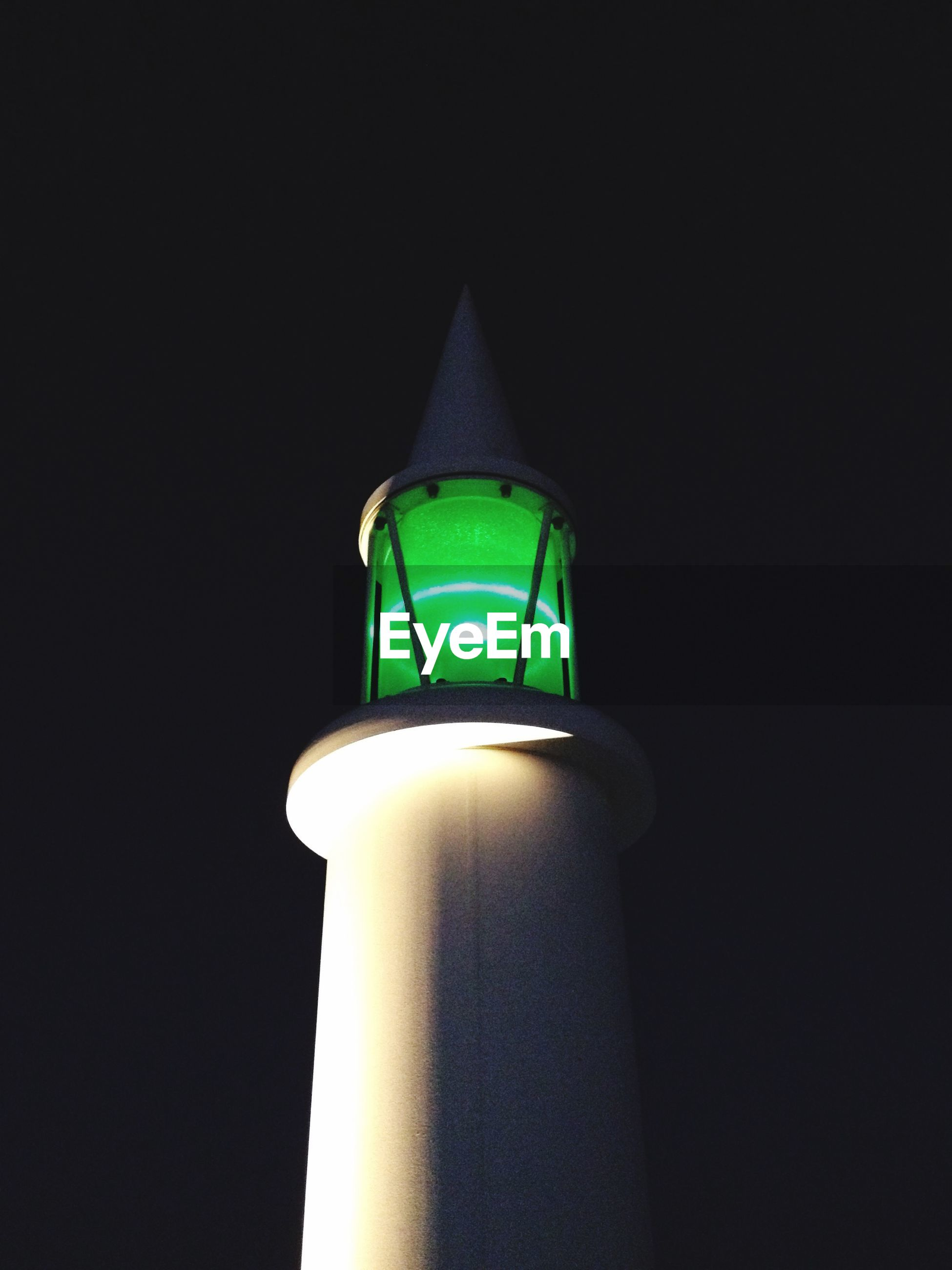 Low angle view of illuminated green light at night