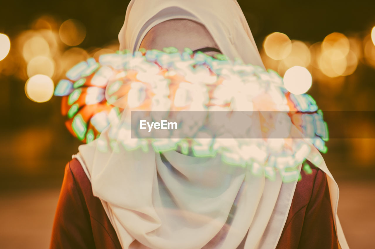 Woman In Hijab Seen Through Glass With Reflection Of Colorful Lights