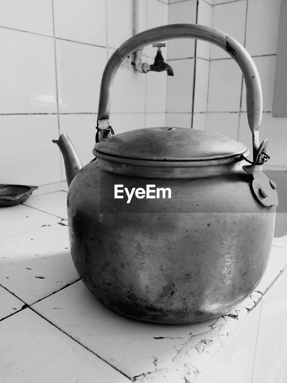 Close-up of kettle on tiled floor