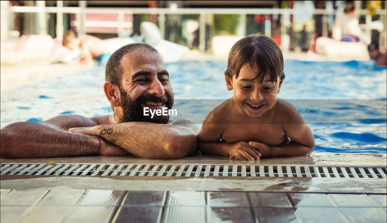 Smiling Shirtless Father With Son Relaxing At Poolside