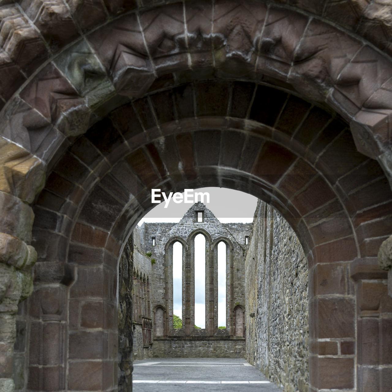 Old ruin seen through arch against sky