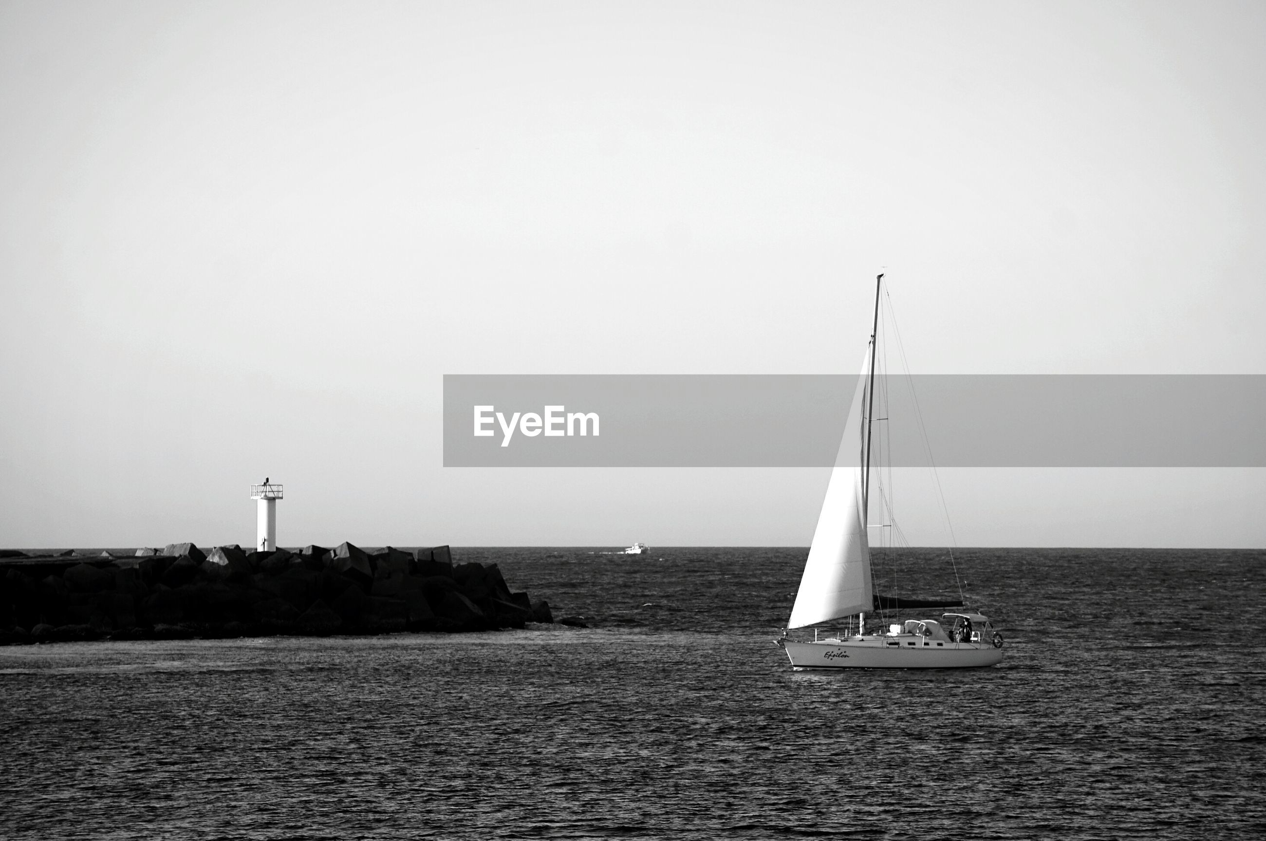 Sailboat sailing in sea by lighthouse against clear sky