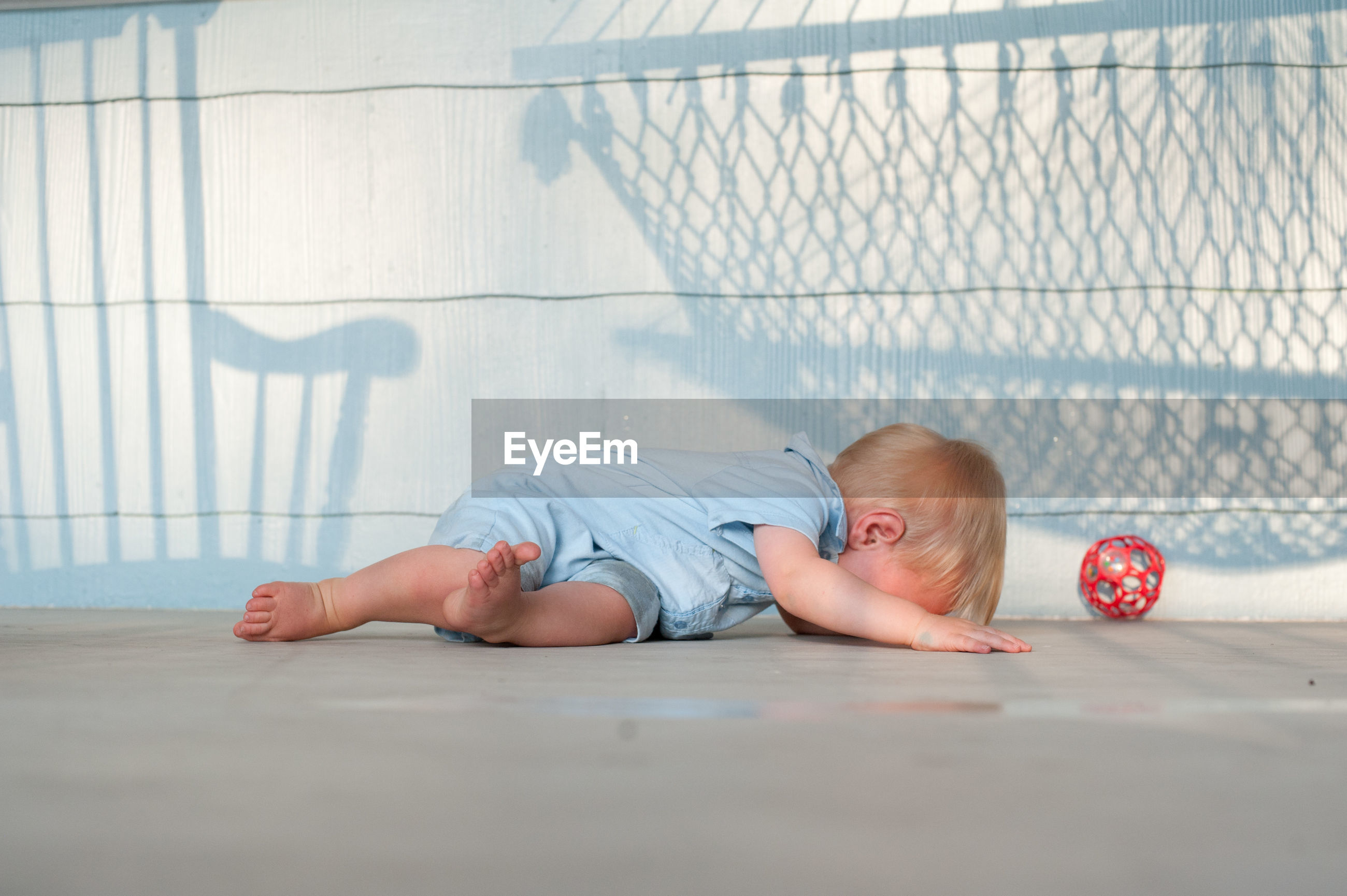 Full length of baby boy crying against wall at porch