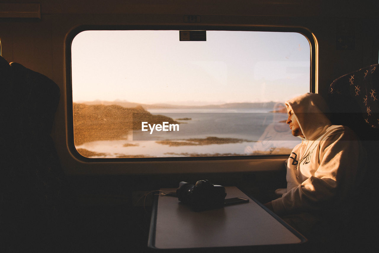 vehicle interior, window, transportation, one person, real people, car interior, airplane, journey, travel, mode of transport, vehicle seat, looking through window, sky, childhood, air vehicle, indoors, day, landscape, boys, sea, flying, nature, people