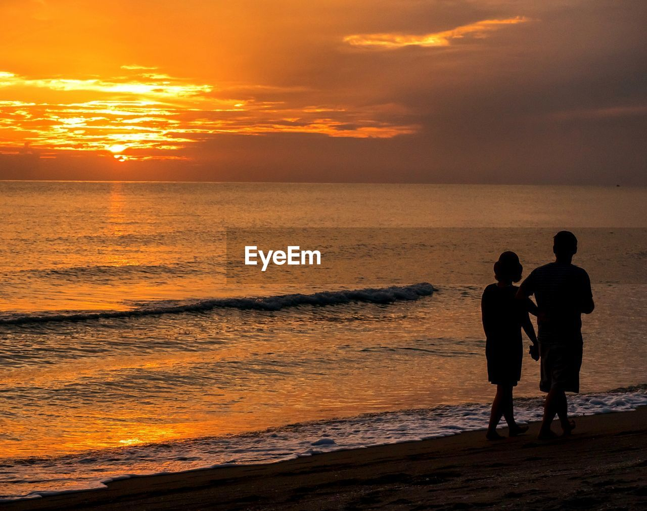 sunset, sky, water, sea, orange color, two people, beach, beauty in nature, cloud - sky, men, real people, scenics - nature, land, togetherness, leisure activity, horizon over water, bonding, standing, horizon, positive emotion, outdoors, couple - relationship