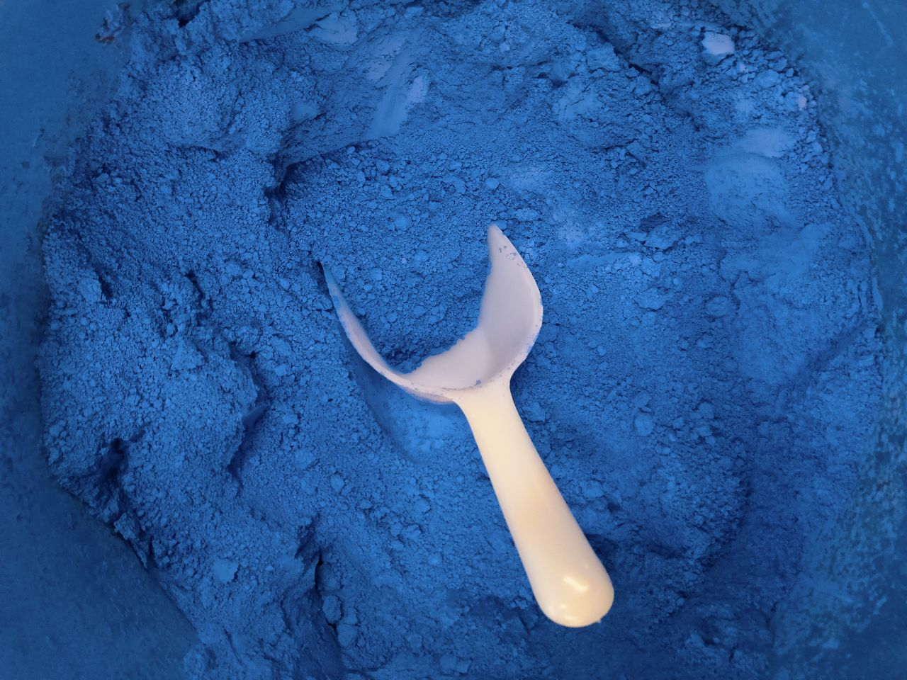 High Angle View Of Blue Powder Paint With Spatula
