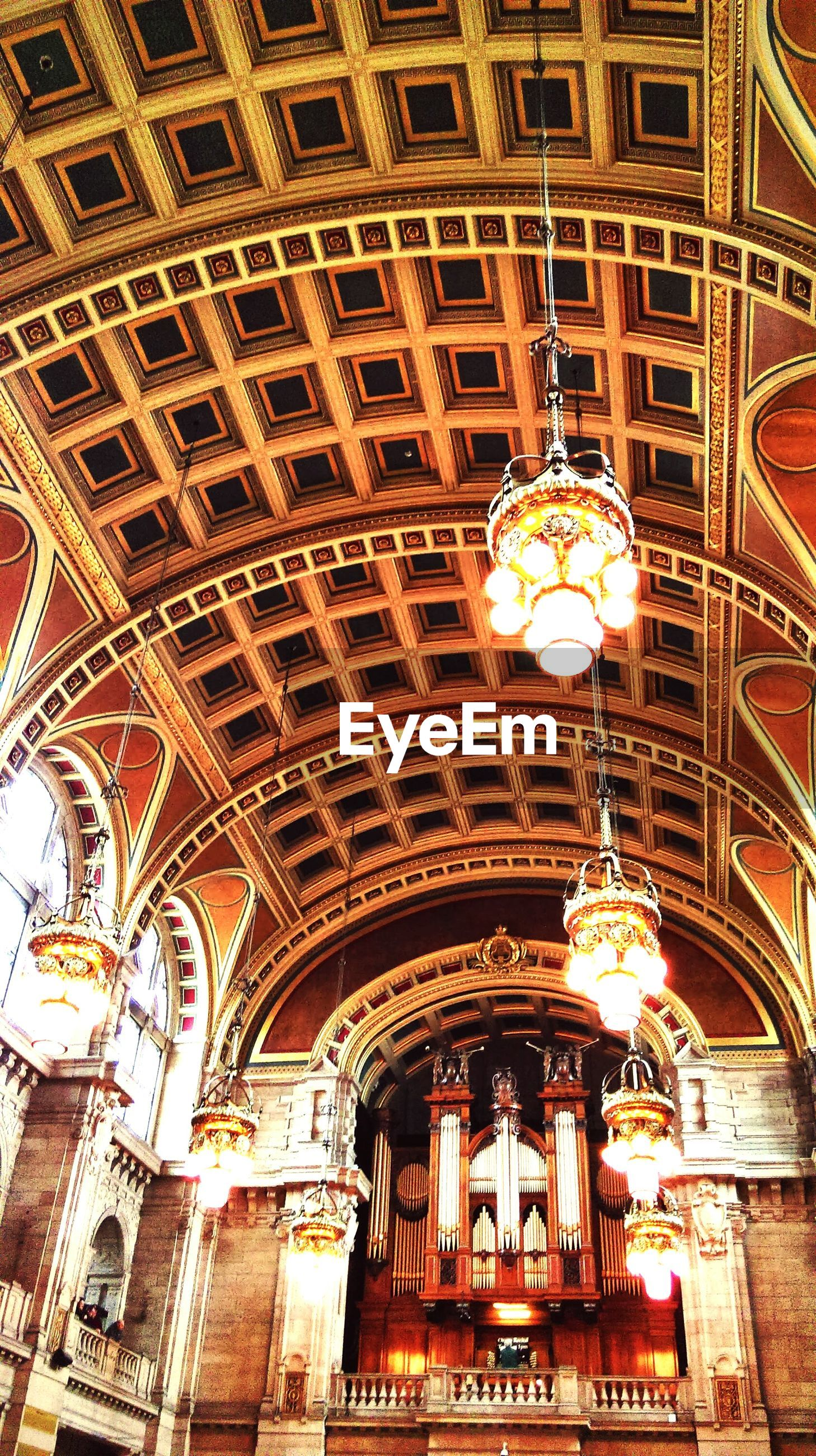 low angle view, architecture, built structure, ceiling, place of worship, illuminated, religion, church, indoors, spirituality, ornate, lighting equipment, chandelier, building exterior, cathedral, architectural feature, design, famous place
